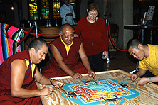 Lucy Casado watches Buddhist monks creating a sand mandala at her restaurant.
